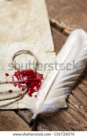 Closeup of a feather and red sealing wax on old wooden table - stock photo
