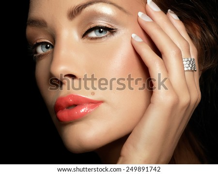 Closeup of a female face with hand wearing a diamond ring.  - stock photo