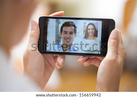 Closeup of a female hand holding a smart phone during a skype video call with her friend  - stock photo