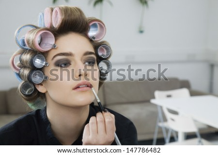 Closeup of a female model in hair curlers applying lip gloss - stock photo