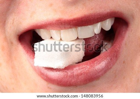 Closeup of a female mouth smiling with a block of white refined sugar between the teeth.