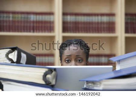 Closeup of a female office worker behind stacks of documents in office - stock photo