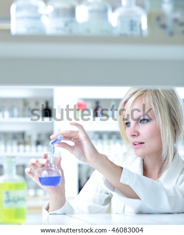 Closeup of a female researcher carrying out experiments in a lab (color toned image) - stock photo