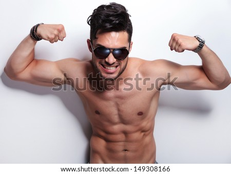 closeup of a fierce young topless man showing his biceps while looking at the camera. on light gray background - stock photo