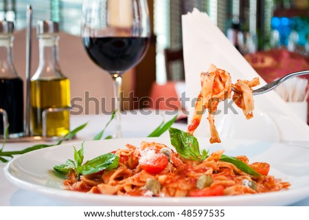 closeup of a fituchini served up with sauce and cherry tomatoes - stock photo
