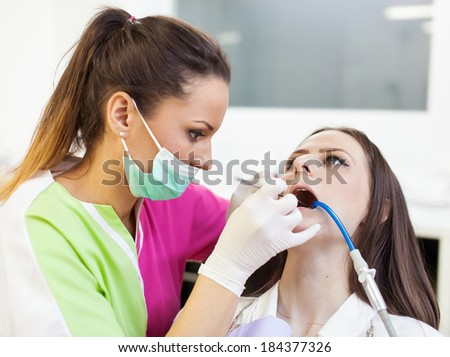 Closeup of a focused woman dentist working on her patient's teeth