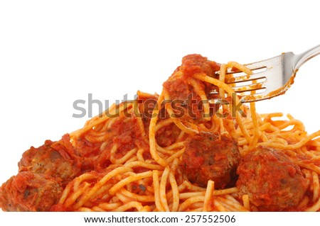 Closeup of a fork with spaghetti and meatballs in tomato sauce - stock photo