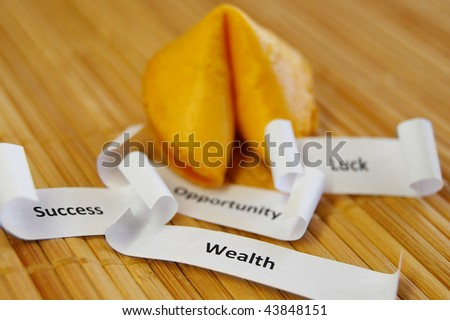 closeup of a fortune cookie with Success, Wealth, Opportunity messages - stock photo