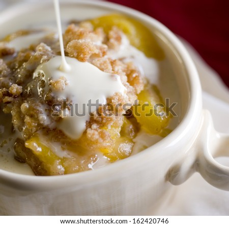 Closeup of a fresh peach cobbler with drizzling maple cream sauce. - stock photo