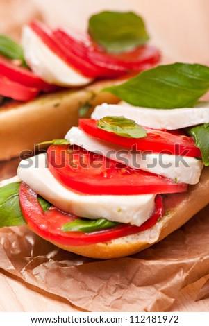 Closeup of a fresh sandwich with mozzarella, tomatoes and basil - stock photo