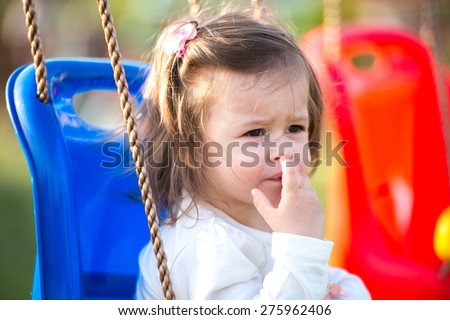 closeup of a girl in a park swing looking - stock photo