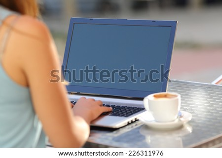 Closeup of a girl typing on a laptop and showing screen in a restaurant terrace - stock photo