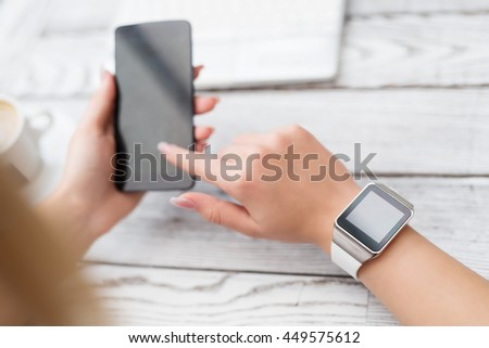 Closeup of a girl wearing a smartwatch. Isolated display. Typing on the mobile phone in the background.