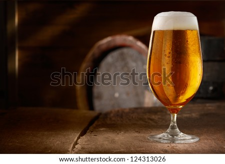Closeup of a glass of fresh foamy beer on a table in a vintage beer cellar - stock photo