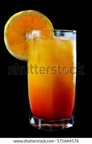 Closeup of a glass of iced tropical orange and rum cocktail garnished with a slice of fresh orange over a black background - stock photo