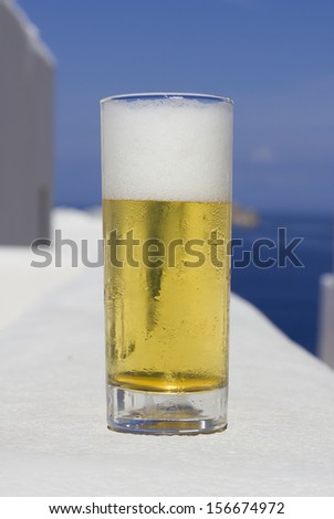 closeup of a glass with fresh beer in front of the sea