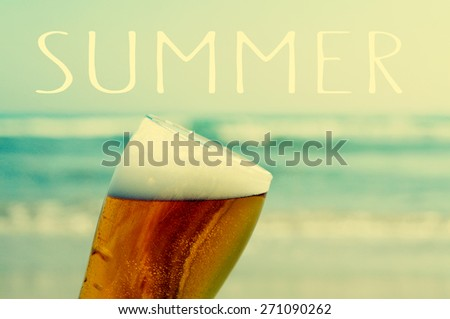 closeup of a glass with refreshing beer and the word summer with the ocean in the background - stock photo