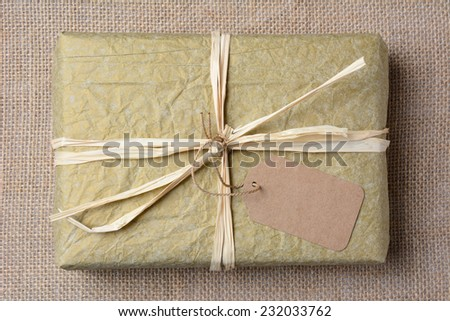 Closeup of a gold tissue paper wrapped present on a burlap surface. The gift is tied with raffia and a blank git tag. High angle shot in horizontal format.  - stock photo