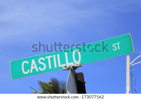 Closeup of a green and white public Castillo Street sign with a sunny blue sky background in Fort Lauderdale, Florida.