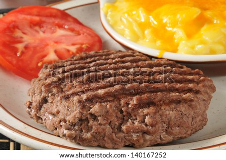 Closeup of a grilled ground sirloin patty with au gratin potatoes - stock photo