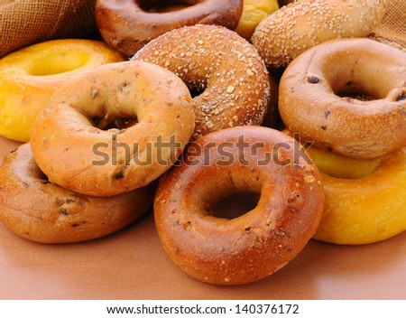Closeup of a group of assorted bagels on a wood table top with burlap in the background. Bagels include, egg, whole grain, cinnamon raisin, sesame seed - stock photo