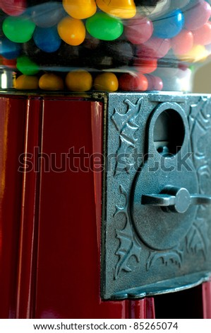 Closeup of a gumball machine with candy and penny slot - stock photo