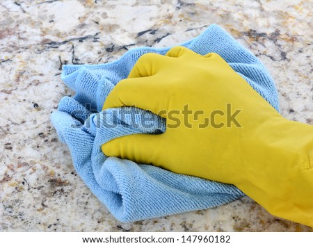 Closeup of a hand in a yellow latex glove using a blue towel to clean a counter top. - stock photo