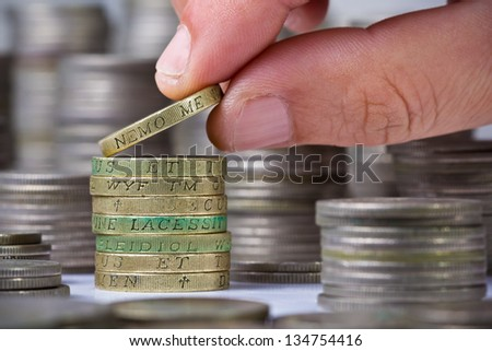 Closeup of a hand places a coin onto a british pound coins stack - stock photo