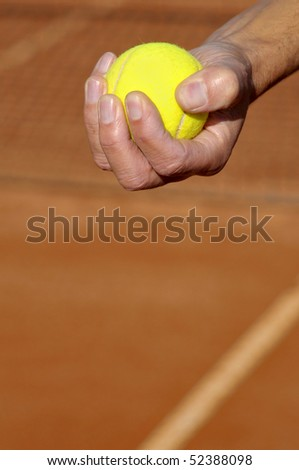 Closeup of a hand with a tennis ball in a clay court - stock photo