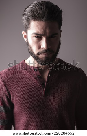 Closeup of a handsome beard man in burgundy sweater, looking at the camera, on grey background - stock photo
