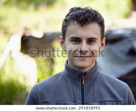 Closeup of a handsome teenage boy in the countryside - stock photo