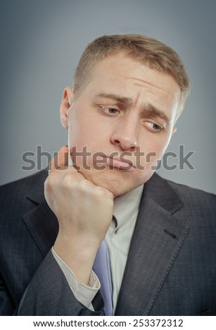 Closeup of a handsome young business man thinking, melancholy, sad - stock photo