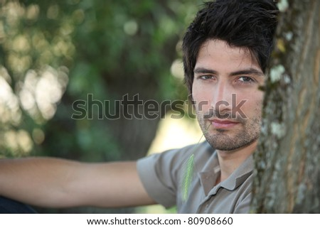 Closeup of a handsome young man sitting amongst the trees - stock photo