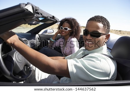 Closeup of a happy African American couple driving convertible on desert road - stock photo