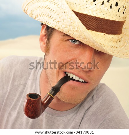 Closeup of a happy brutal young man looking at camera and smoking his pipe. American farmer