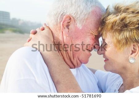 Closeup of a happy senior couple romancing on a beach - stock photo