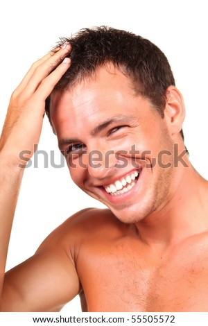 Closeup of a happy young man looking at camera and touching his hair - stock photo