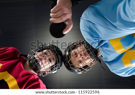 Closeup of a hockey faceoff with teenage hockey players and puck - stock photo