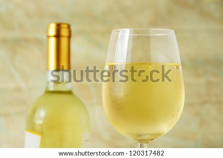 Closeup of a ice cold glass of italian white wine covered with water drops - condensation, selective focus - stock photo