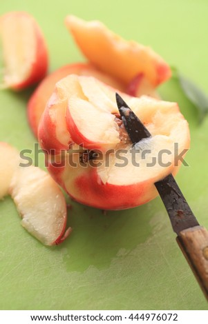 Closeup of a knife cutting into a juicy white peach - stock photo