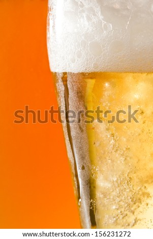 closeup of a light refreshing lager served in a cold pint with an amber beer on the background