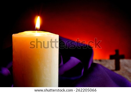 closeup of a lit candle with a purple drapery in the background and a Christian cross, on a wooden rustic surface and a red lighted background - stock photo