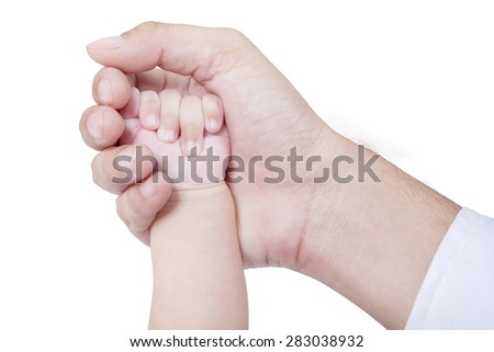 Closeup of a little baby hand protected by father hand, isolated on white background
