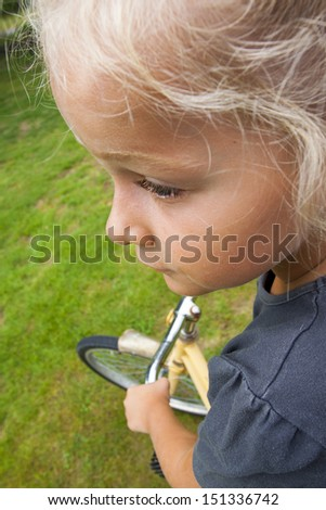 Closeup of a little girl learning to ride a bike - stock photo