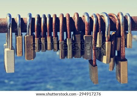 closeup of a lot of rusty padlocks locked in the crossbar of a rusty railing near the sea - stock photo