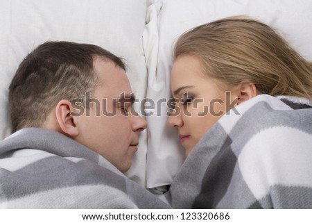 Closeup of a loving couple sleeping on the bed - stock photo