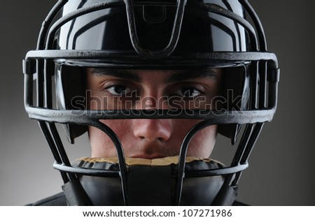 Closeup of a male baseball catcher with his protective mask on. Horizontal format with a light to dark gray background. - stock photo