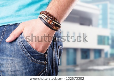 Closeup of a male standing with his hand in his pocket - stock photo
