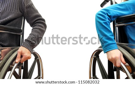 closeup of a man and a kid on wheelchairs each on their side - stock photo