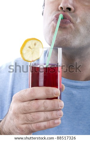closeup of a man drinking a red cocktail with a straw - stock photo